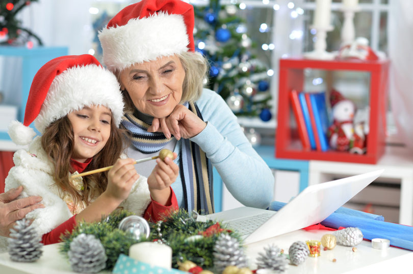 Portrait of grandmother and her granddaughter preparing for Christmas at home